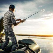 Рыбак на лодке со спиннингом